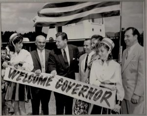 "People with American Flag holding a ""Welcome Governor"" sign"